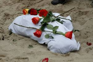 We wrapped their bodies in white sheets and placed roses on their remains.  The remains of Jake (named by Alec Pedersen who held him during the ceremony after his son) are pictured here.  [image credit: Diana Lannes]